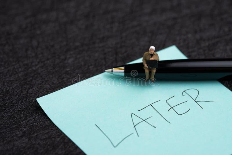 Miniatuurzakenmanzitting op pen en kleverige nota met hand die het woord later op donkere zwarte achtergrond schrijven die zoals  royalty-vrije stock foto's