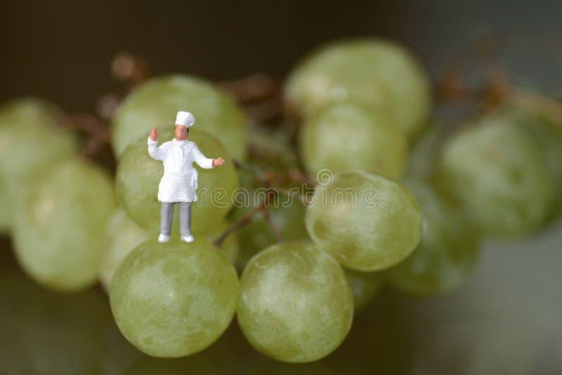 Miniatyr av en kock med druvor royaltyfria foton
