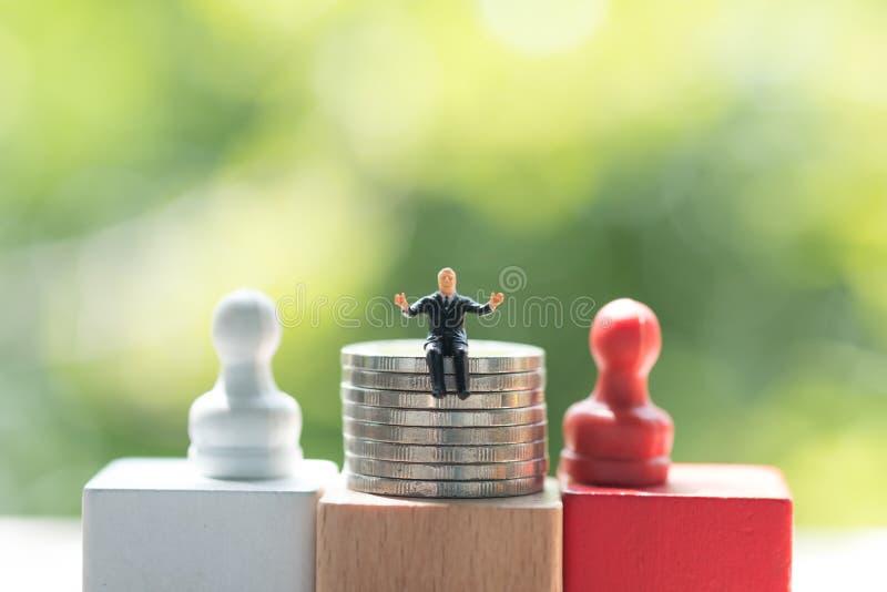 Miniatyraffärsman som sitter på bunt av mynt fotografering för bildbyråer