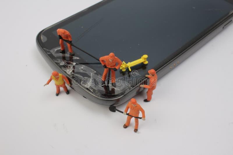 Miniatyrarbetare som kontrollerar den generiska mobiltelefonen royaltyfria foton