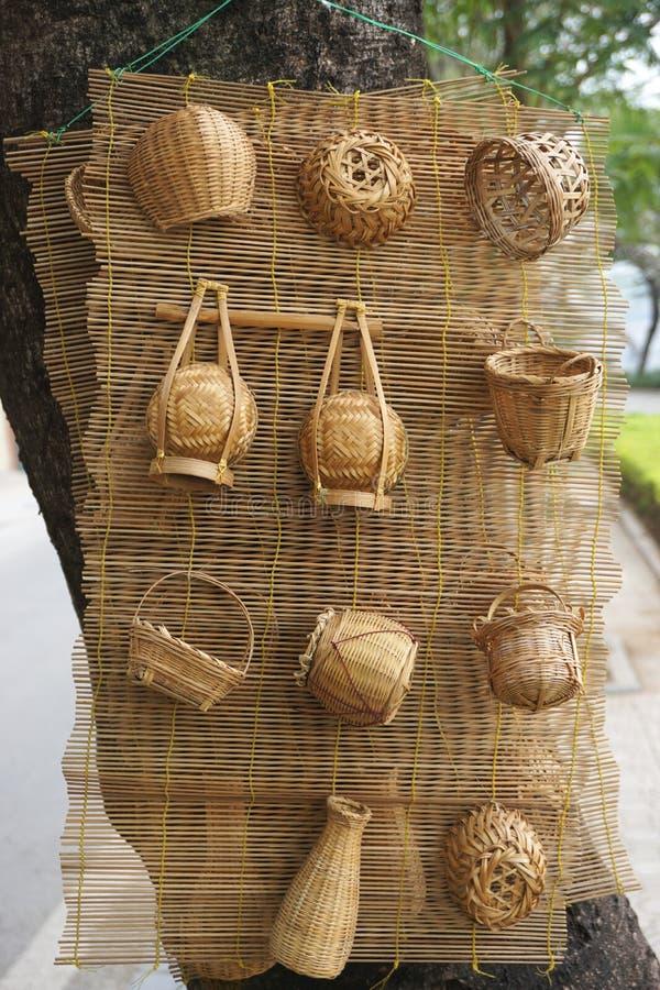Miniatyrbambukorgar som hänger på ett vävt mattt på ett träd i stads- Hanoi, Vietnam arkivbild