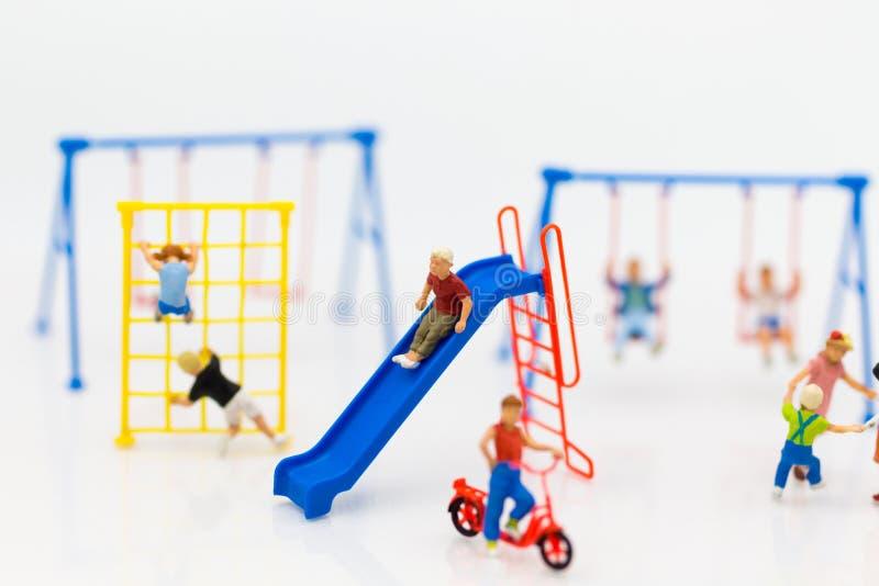 Miniatyrbarn: Pojken spelar glidaren lyckligt med vännen på lekplats Bildbruk för dag för barn` s royaltyfria foton