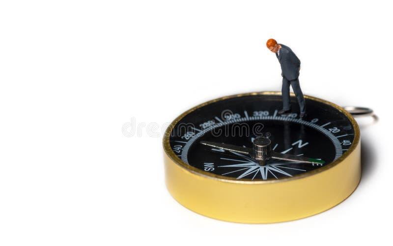 Miniatyrdiagram affärsman i mörkt - blått dräktanseende på den guld- kompasset för att finna vägen hur till framgång av affären o arkivfoton