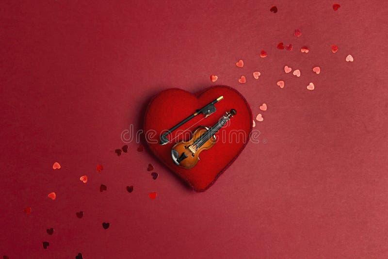 Miniatyrfiol på hjärtan på den röda bakgrunden Förälskelse för musikbegrepp arkivbild