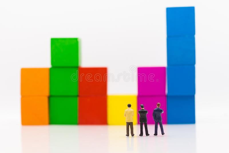 Miniatyrfolk: Affärsmän som står och ser till grafer, stiger från affärsvinster Använda som affärsidé arkivfoton