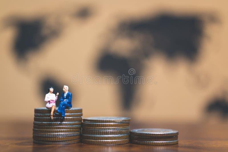 Miniatyrfolk: Affärsman på bunt av mynt, pengar och financ arkivfoton