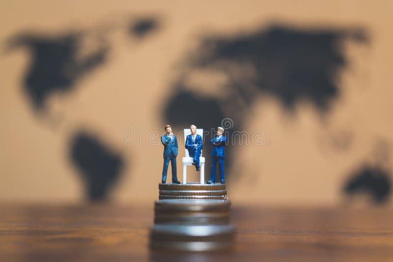 Miniatyrfolk: Affärsman på bunt av mynt, pengar och financ arkivbilder