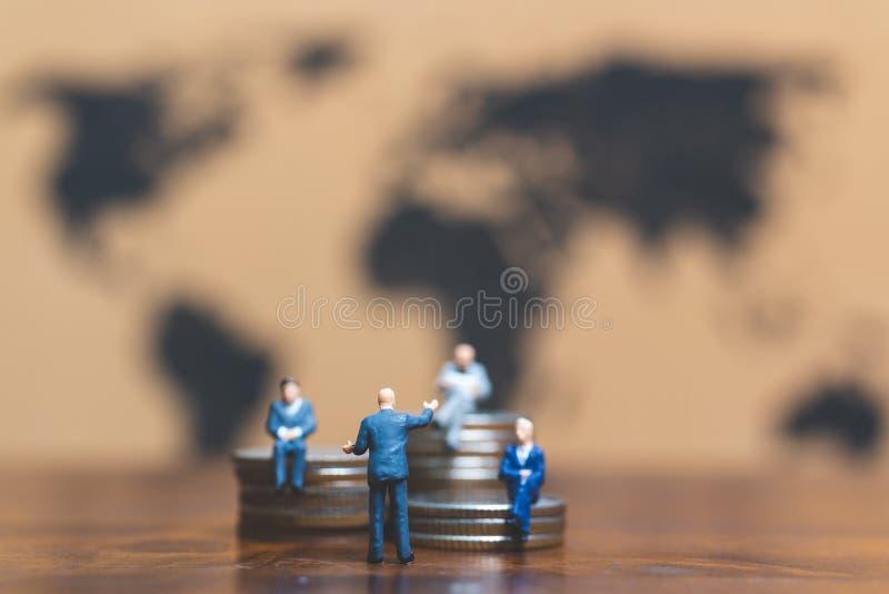 Miniatyrfolk: Affärsman på bunt av mynt, pengar och financ arkivfoto