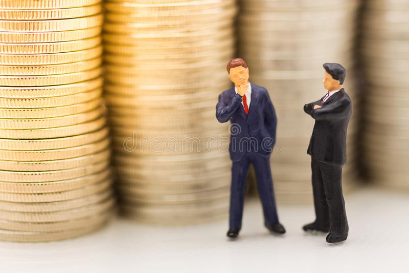 Miniatyrfolk, affärsman som söker efter bunten av mynt genom att använda som bakgrundspengartillväxt upp, sparande som är finansi arkivbilder