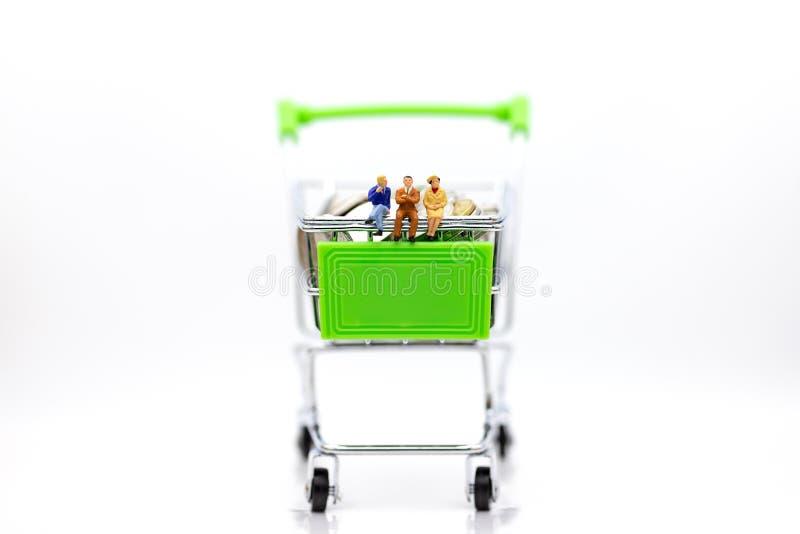 Miniatyrfolk: Affärsman som sitter på shoppingvagnen på bunt av myntet Bildbruk för återförsäljnings- affärsidé royaltyfri fotografi