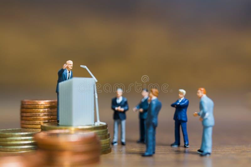 Miniatyrfolk: Affärsman som talar på podiet arkivfoto