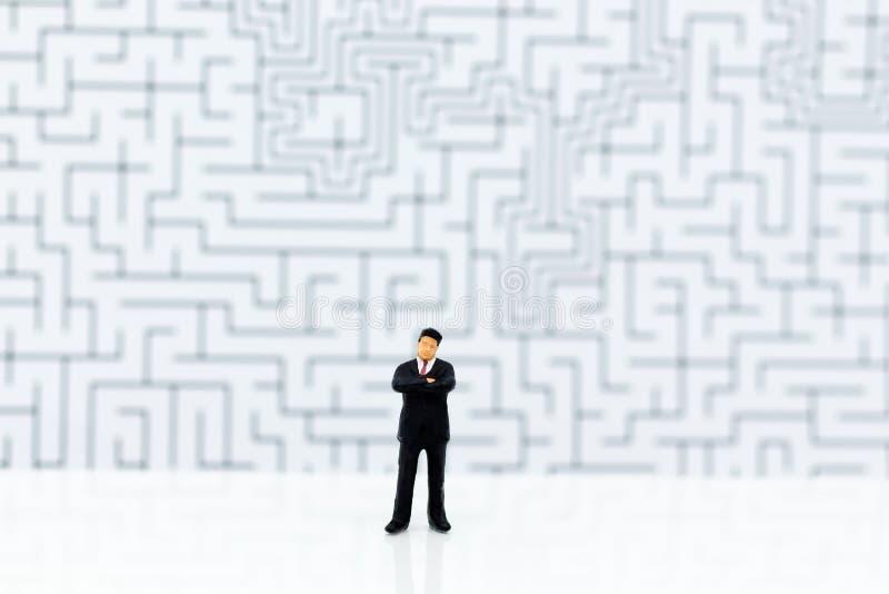 Miniatyrfolk: Affärsmananseende med en labyrint till bakgrund Bildbruk för fyndlösningen, affärsidé arkivbilder
