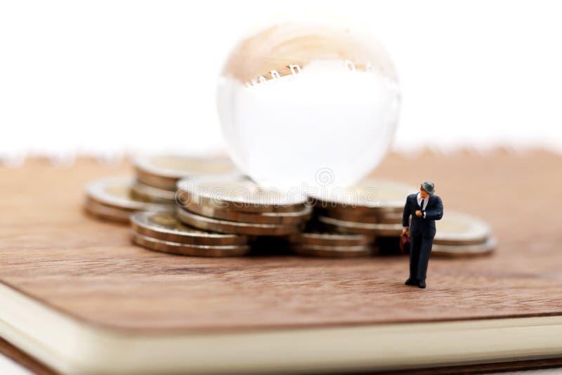 Miniatyrfolk: Affärsmananseende på boken med moment av myntet royaltyfri foto