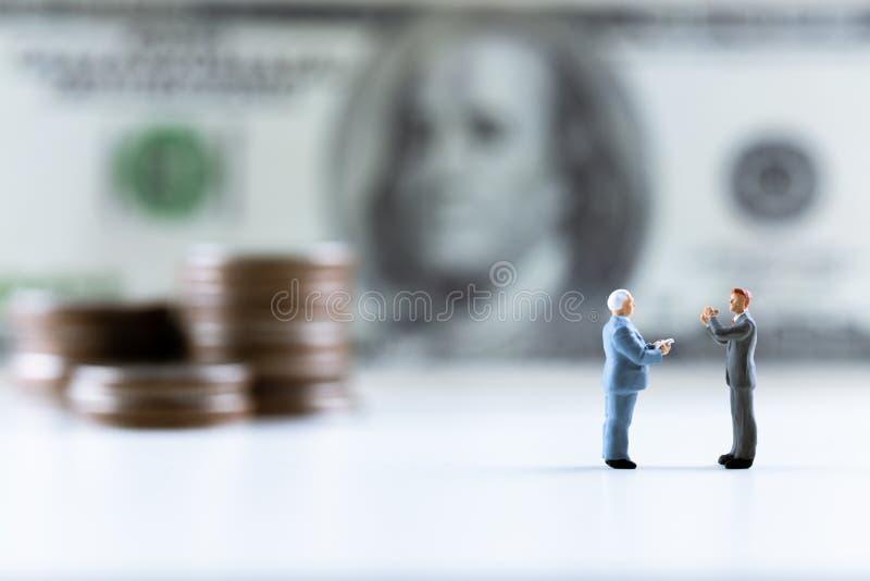 Miniatyrfolk, affärsmananseende på dollarräkning med myntbuntmoment upp bakgrund fotografering för bildbyråer