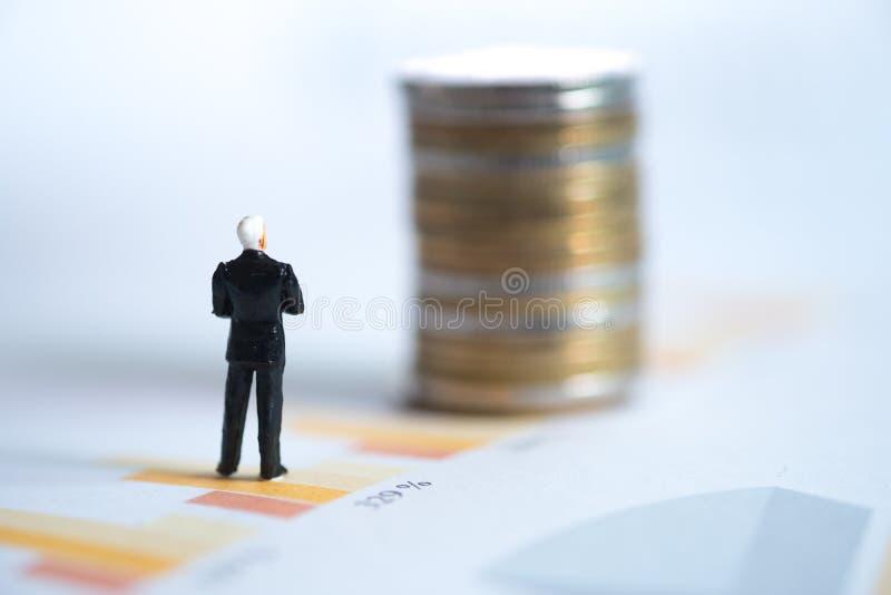 Miniatyrfolk: Affärsmananseende på graf med att se till mynt arkivfoto