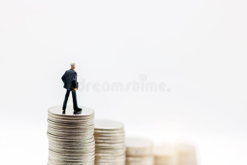 Miniatyrfolk: Affärsmananseende på moment av myntpengar C royaltyfri foto