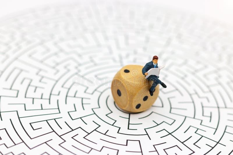 Miniatyrfolk: Affärsmanläsning på mitt av labyrint Begrepp royaltyfri bild