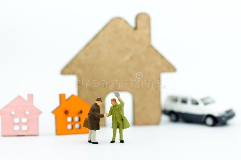 Miniatyrfolk: Affärsmannen gör avtalet för lån, köper huset Bildbruk för finans, affärsidé royaltyfri foto
