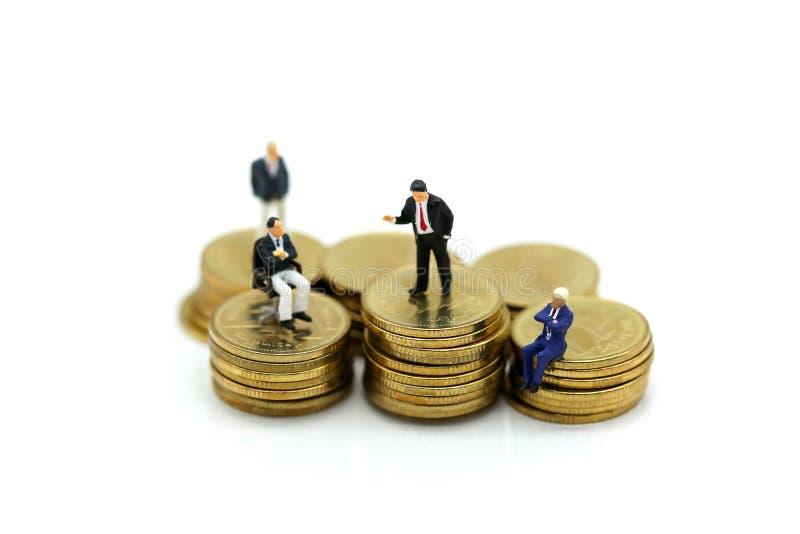 Miniatyrfolk: Affärsmansammanträde med bunten av mynt och royaltyfri fotografi