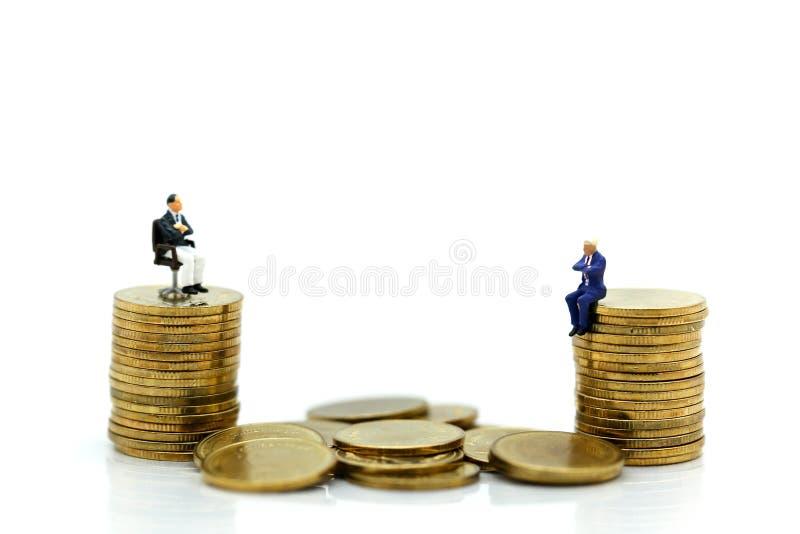 Miniatyrfolk: Affärsmansammanträde på bunten av mynt, affär arkivfoto