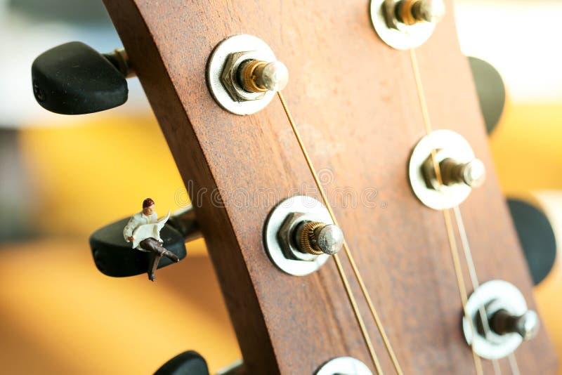 Miniatyrfolk: Affärsmansammanträde på den akustiska gitarren Tid royaltyfri fotografi