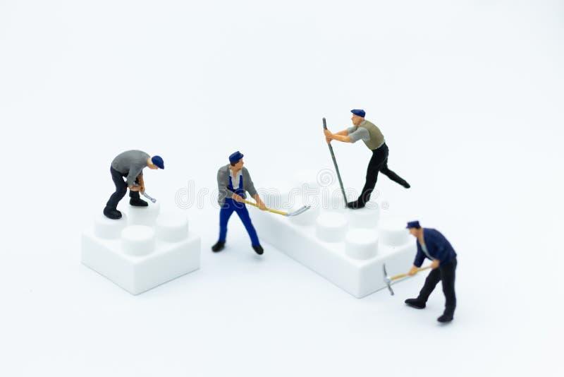 Miniatyrfolk: Arbetare använder hjälpmedel för att borra plast- delar Bildbruk för att demontera apparaten royaltyfri bild
