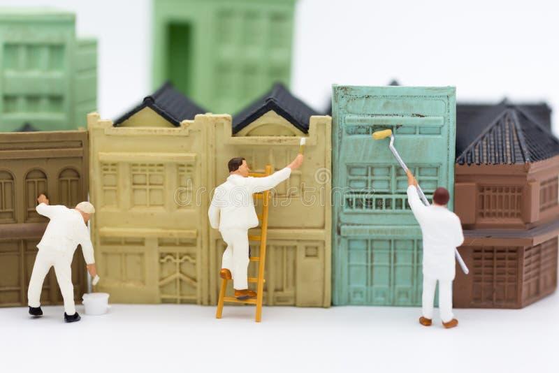Miniatyrfolk: Arbetare målar byggnaden i stad Bildbruk för affärsidé arkivbilder