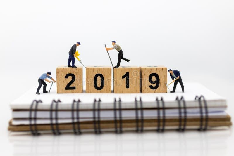 Miniatyrfolk: Arbetare som använder hjälpmedel med träkvarteret 2019 Bildbruk för det nya året, affärsidé arkivfoto
