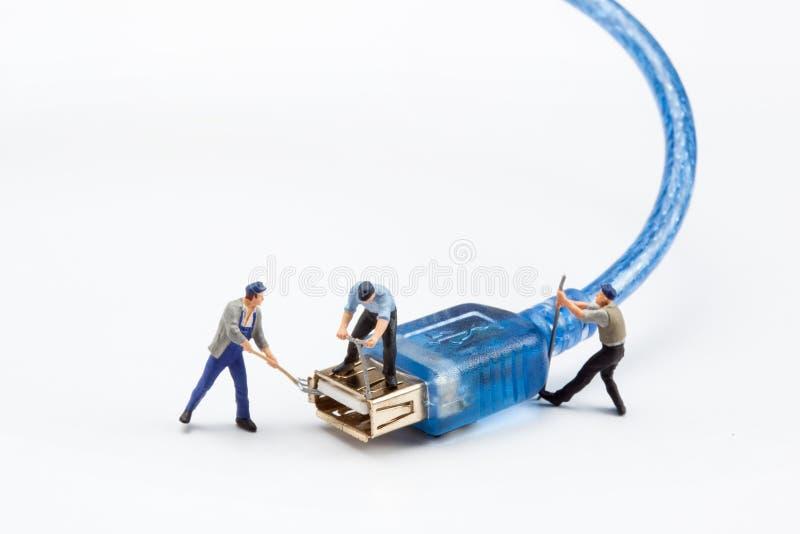 Miniatyrfolk - arbetare som fixar en USB, pluggar royaltyfria bilder