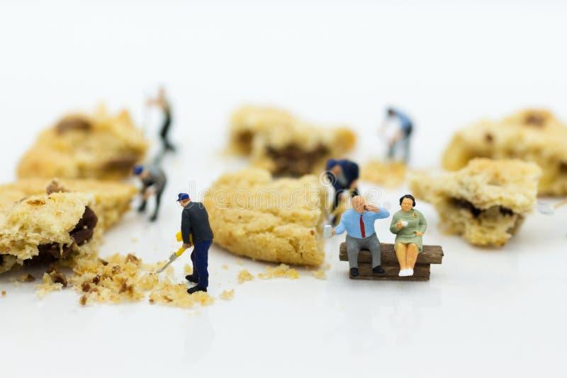 Miniatyrfolk: Arbetare var krossade kakor Bildbruk för bageriaffärsidé arkivbilder
