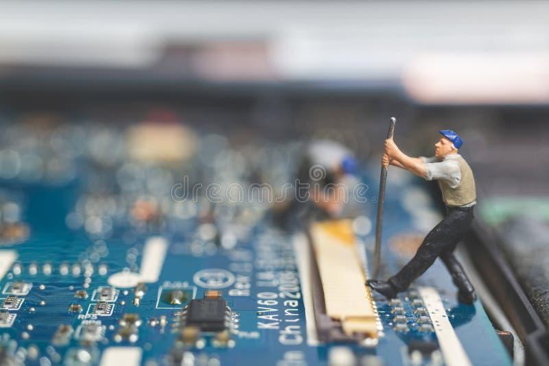 Miniatyrfolk: Arbetarlag av teknikerer som reparerar tangentbord c royaltyfri foto