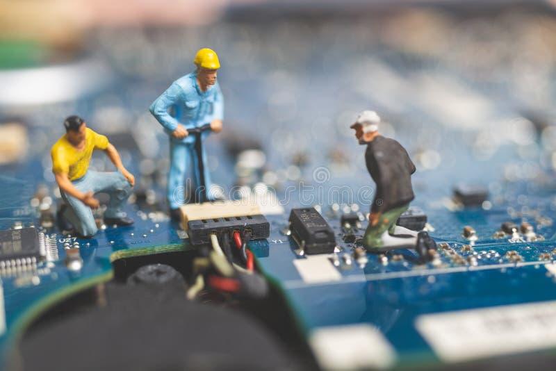 Miniatyrfolk: Arbetarlag av teknikerer som reparerar tangentbord c arkivbild