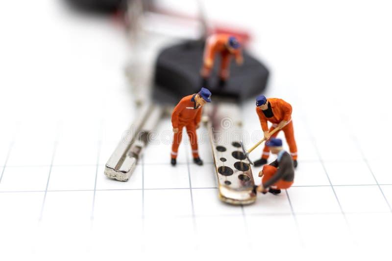 Miniatyrfolk: Bilreparationsarbetare för att retur ska använda Bildbruk för underhåll, garanti, affärsidé royaltyfria foton