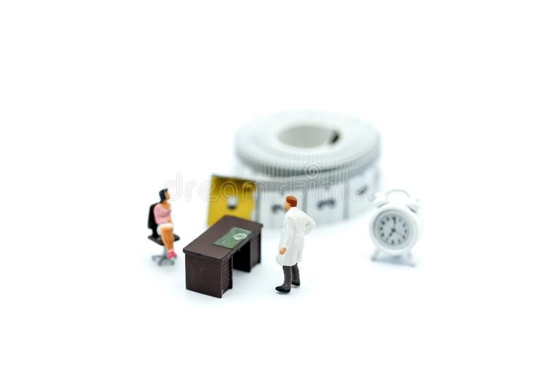 Miniatyrfolk: doktor och kvinna med måttbandet, sjukvård royaltyfria bilder