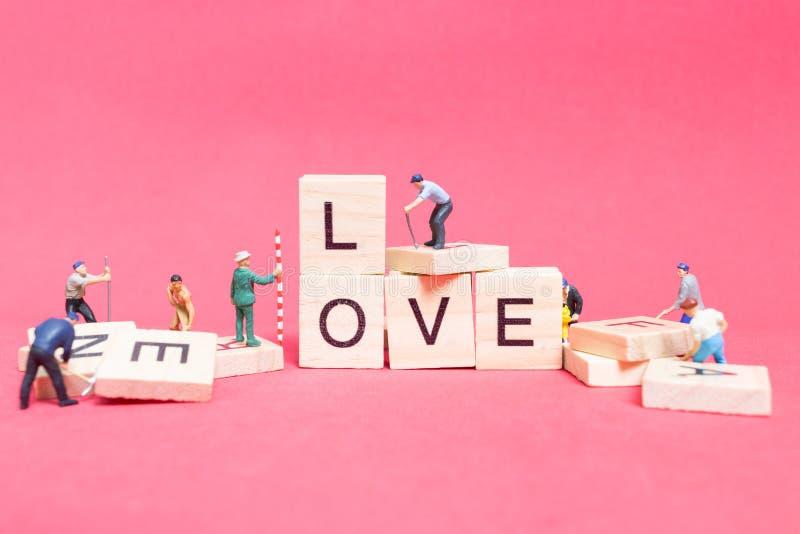 Miniatyrfolk: ` För förälskelse för ` för ord för arbetarlagbyggnad, arkivbild