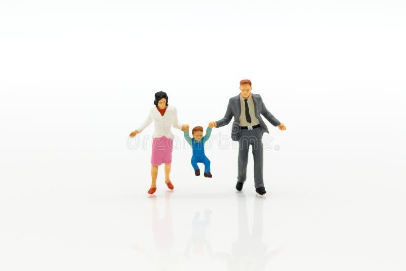 Miniatyrfolk: Familjdiagram anseende på det vita golvet Avbilda bruk för bakgrundsavgångplanläggningen, livförsäkringbegrepp royaltyfria bilder