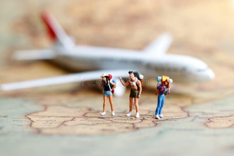 Miniatyrfolk: fotvandrare med flygplanet, lopp och affär arkivfoto