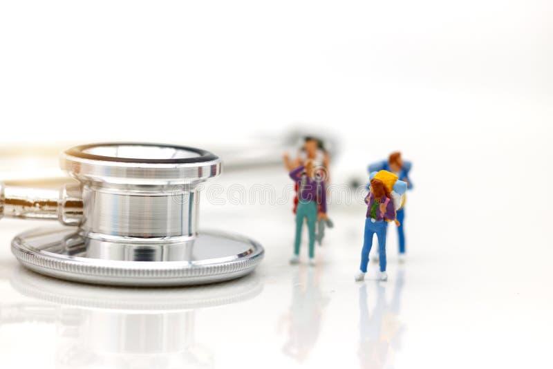 Miniatyrfolk: Fotvandrare som framme går av stetoskopet royaltyfri bild