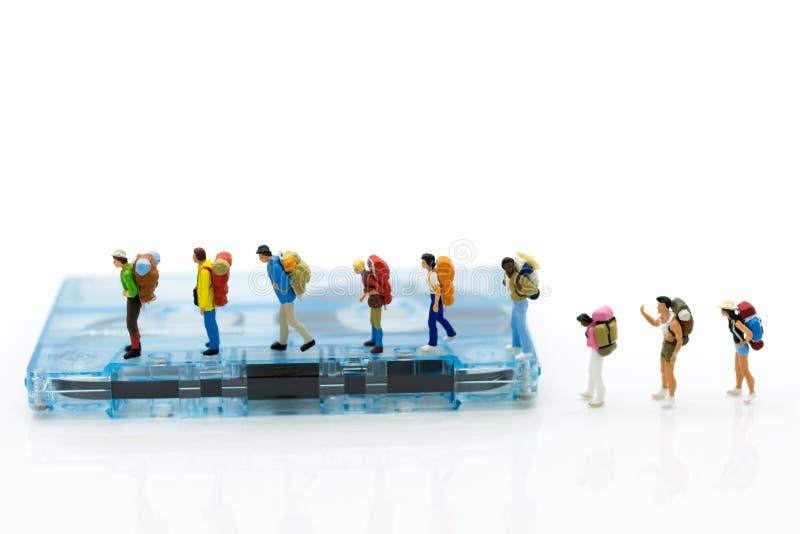 Miniatyrfolk: fotvandrare som går på den kompakta kassetten Avbilda bruk för musik av loppet, affärsidé arkivbilder