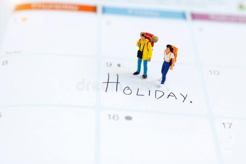 Miniatyrfolk: Fotvandrareanseende på kalender arkivbilder