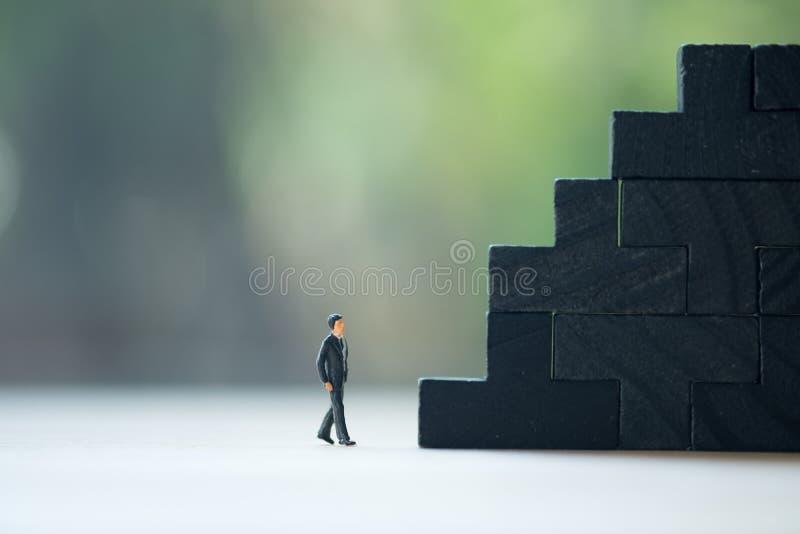 Miniatyrfolk: Gående moment för affärsman till att rangordna affär arkivfoto