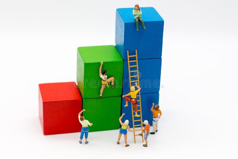 Miniatyrfolk: Gruppidrottsman nen använder trappa för att klättra färgrik wood byggnad Avbilda bruk för aktiviteter, loppet, affä royaltyfri bild