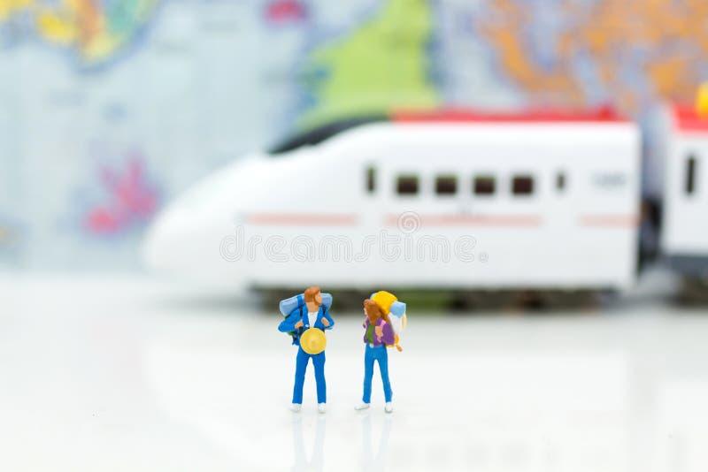 Miniatyrfolk: handelsresande med det väntande på drevet för ryggsäck Ima royaltyfri foto