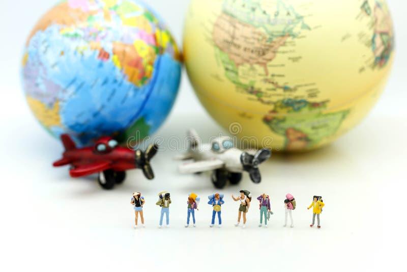 Miniatyrfolk: Handelsresande med världsjordklotet och flygplanet, tra arkivbild
