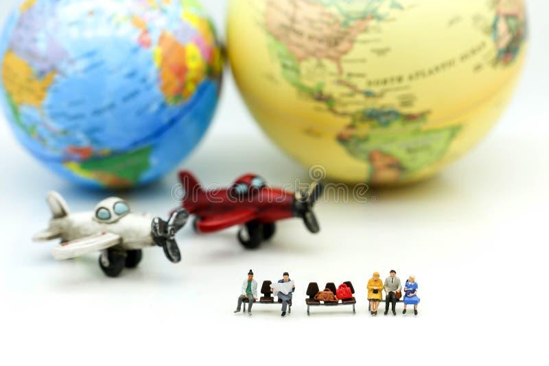Miniatyrfolk: Handelsresande med världsjordklotet och flygplanet, tra royaltyfria foton