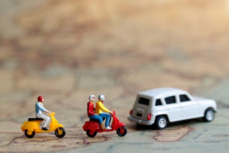 Miniatyrfolk: Handelsresande som rider en motorcykel på översikt med bilen, arkivbild