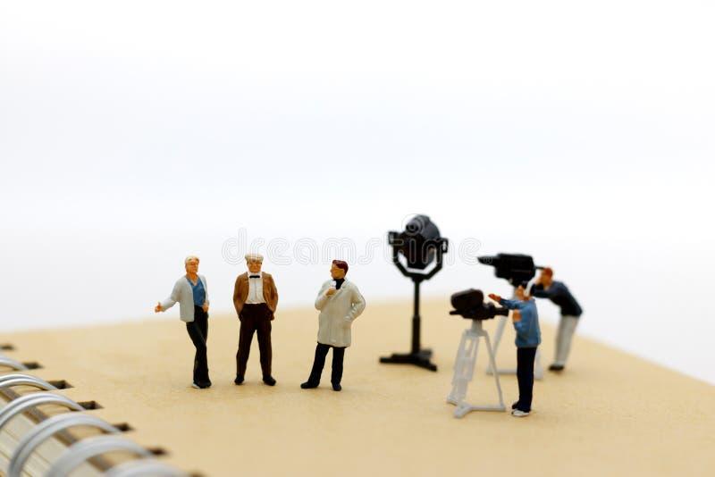 Miniatyrfolk: kvinnlig journalist som gör en intervju en man arkivfoton