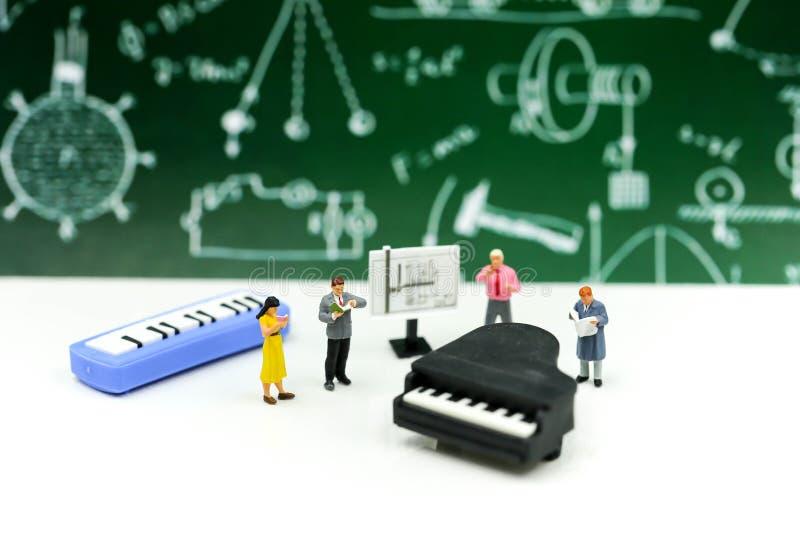 Miniatyrfolk: Lärare och student med pianogrupp av musik royaltyfri foto