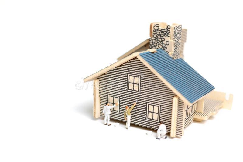 Miniatyrfolk: Målarpensel som målar trähuset arkivfoto