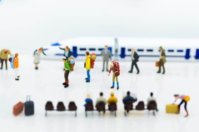 Miniatyrfolk: Många handelsresande som traveing med drevet på drevstationen Bildbruk för loppaffärsidé royaltyfri foto
